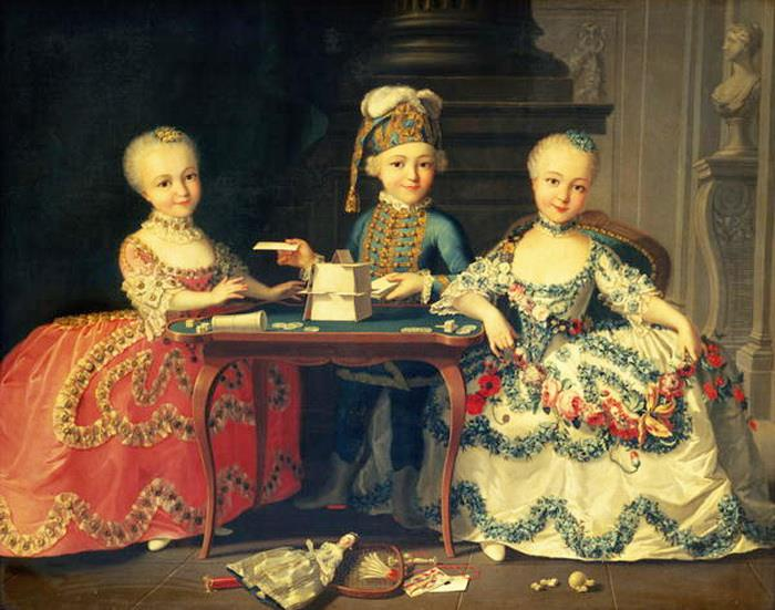 Group portrait of a boy and two girls building a house of cards with other games by the table